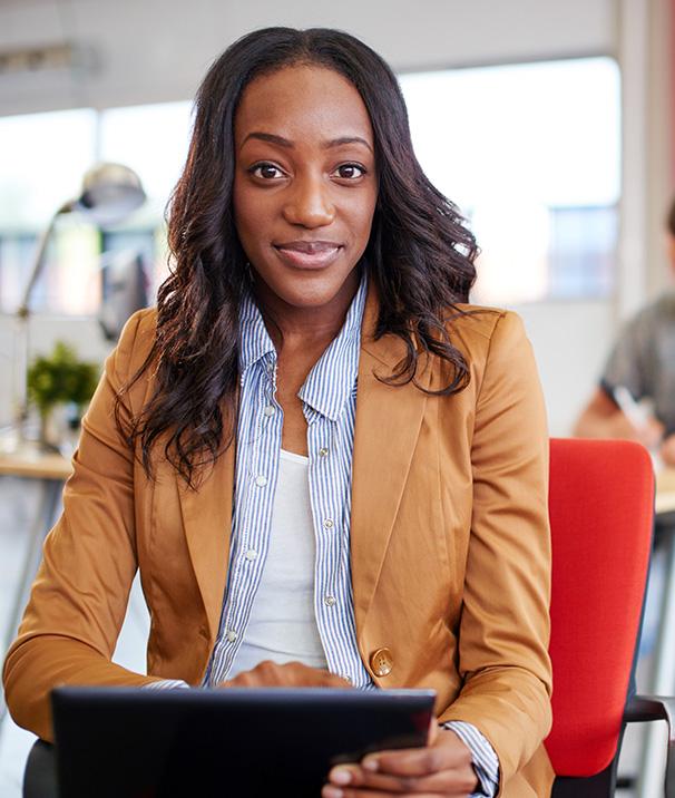 Uma mulher negra sentada em uma cadeira vermelha com um notebook preto no colo, navegando pela internet